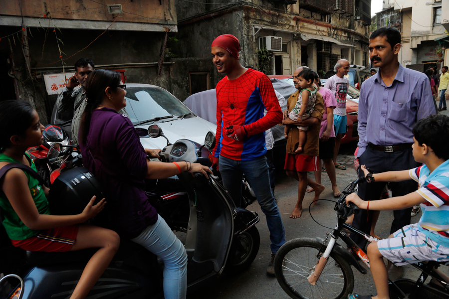 Gaurav Sharma, locally known as Indian Spiderman who is contesting as an independent candidate in the upcoming parliamentary elections waves to children during his campaign in Mumbai, India