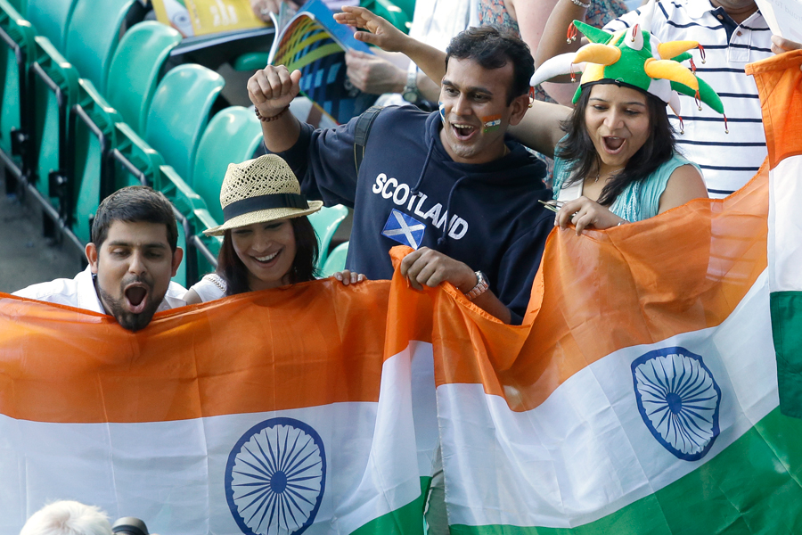 Indian fans wave their national flag and cheer as they wait for the opening ceremony for the Commonwealth Games 2014 in Glasgow, Scotland