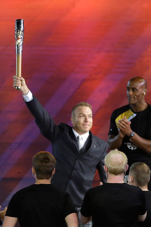 Sir Chris Hoy holds up the Queen's baton during the opening ceremony for the Commonwealth Games 2014 in Glasgow, Scotland