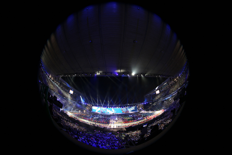 An image taken with a fisheye lens shows a general view of the stadiums as the teams march in during the opening ceremony