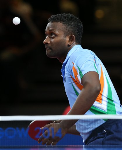 India's Arputharaj Anthony, foreground serves, against Singapore's Ning Gao and Hu Li during the Men's doubles Table tennis final with Sharath Kamal Achanta
