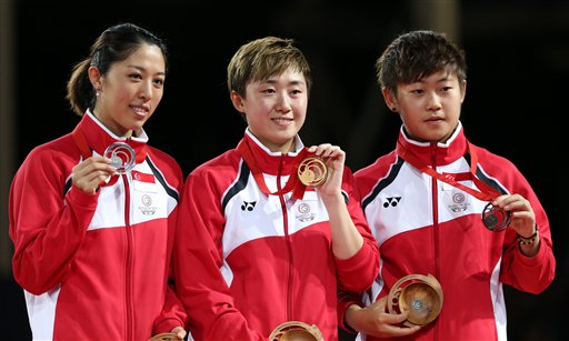 Singapore medal winners, gold medal winner, Tianwei Feng, centre, Mengyu Yu, at left who won silver, and Ye Lin, right, who won bronze, display their medals after the Women's singles Table tennis
