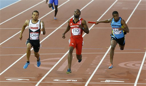 Members of the men's 4 by 100i really teams from Trinidad and Tobago, centre, Bahamas, right and Canada cross the line after they completed their round one heat in the event at Hampden Park stadium