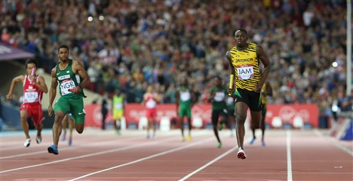 Usain Bolt of Jamaica, right, brings the baton home as he runs the last leg of his first round heat of the men's 4 by 100 meter relay in Hampden Park stadium