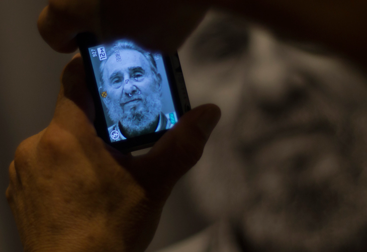 A man takes a picture of a photograph of former Cuban President Fidel Castro during a photo exhibit of Castro made