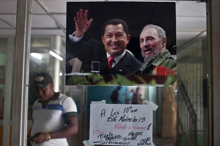 A poster that features Venezuela's late President Hugo Chavez and Cuba's Fidel Castro is displayed on a glass window at the entrance of an apartment building in Havana, Cuba