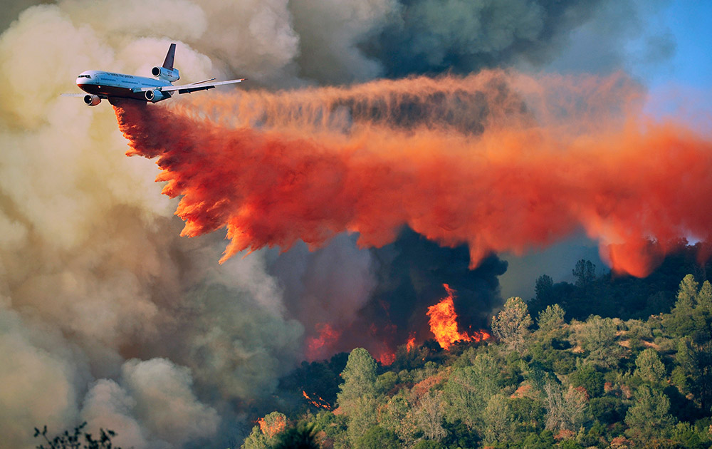 An air tanker drops fire retardent on a fire which was burning on a ridge northeast of Oakhurst, Calif.