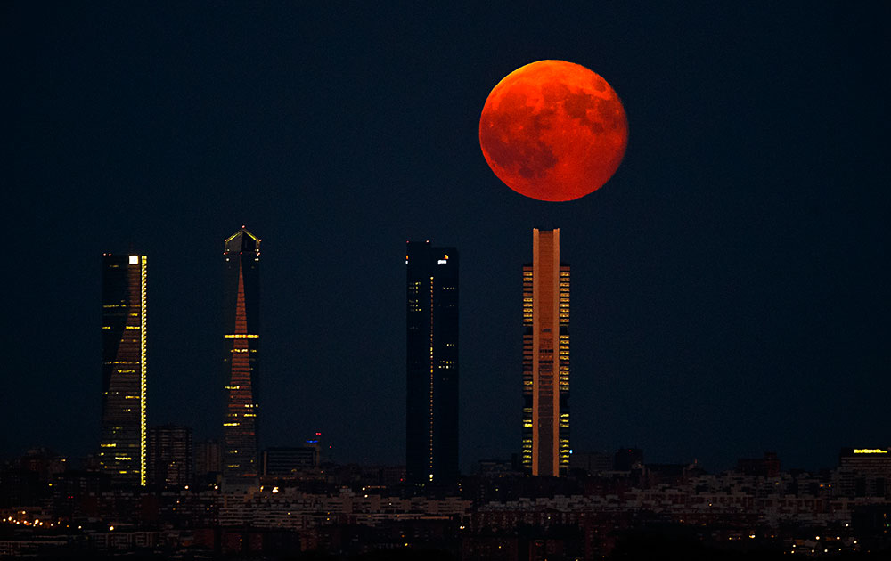 The moon rises in the sky as seen through the Four Towers or C.T.B.A. (Cuatro Torres Business Area), one of the main symbols of Madrid.