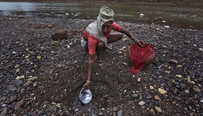গুজরাতের এক মহিলা নদীর পার থেকে পানীয় জল সংগ্রহ করছে